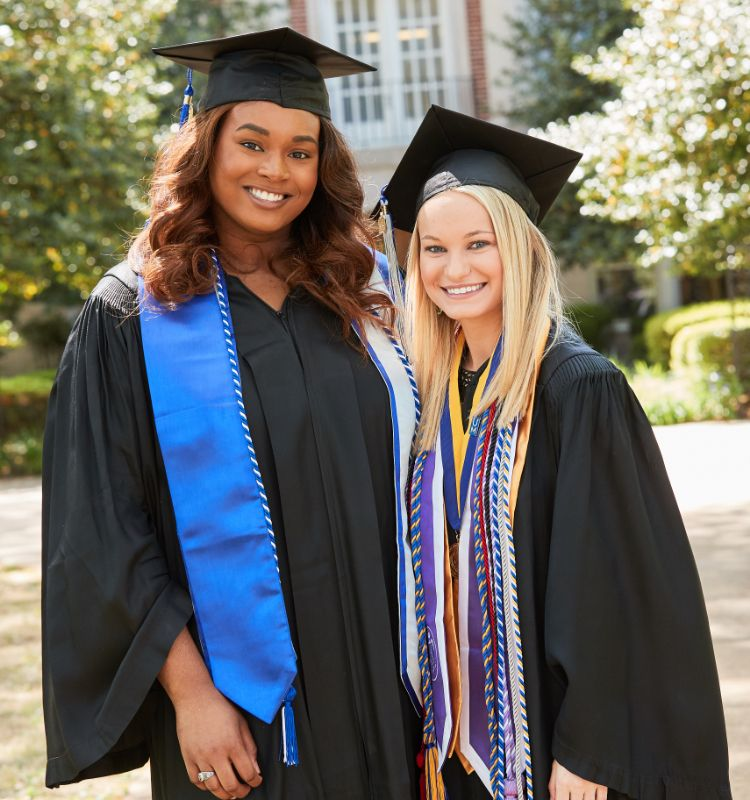 Two students in graduation cap and gown